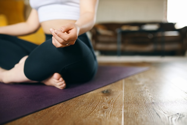 Cropped image of fit muscular young female in sports clothes meditating on floor in half lotus pose, making mudra gesture, sitting on mat before yoga practice, concentrating on feelings and breathing