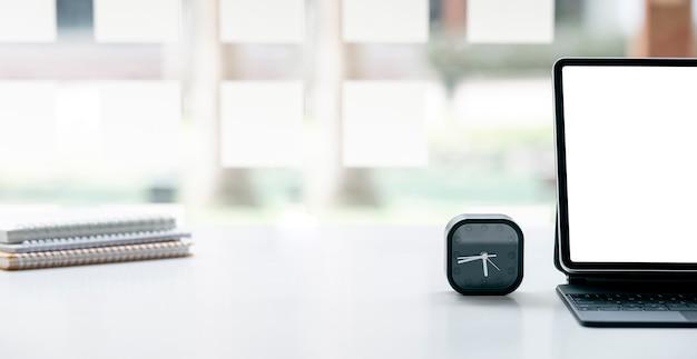 タブレットとキーボード、目覚まし時計と白いテーブルの上のノートブック、コピースペースで背景のトリミングされた画像。