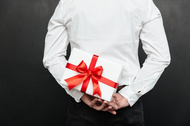 Cropped image from back of man holding white present box with red bow in hands, isolated over dark gray wall