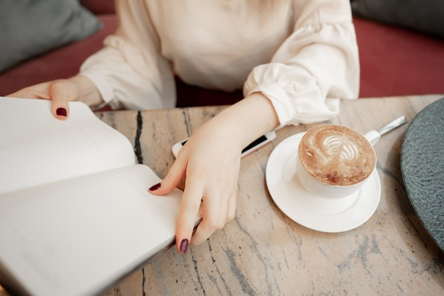 Cropped image of girl making notes in open notepad while sitting at table and resting in modern cozy cafe