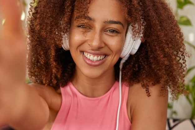 Cropped image of glad mixed race black woman with crisp hair, makes selfie portrait, listens audio track in headphones, being in high spirit, has spare time afer classes, enjoys exciting audio book