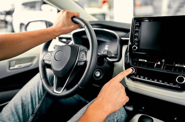 Cropped image hand of man using navigation system or dashboard while driving a car.