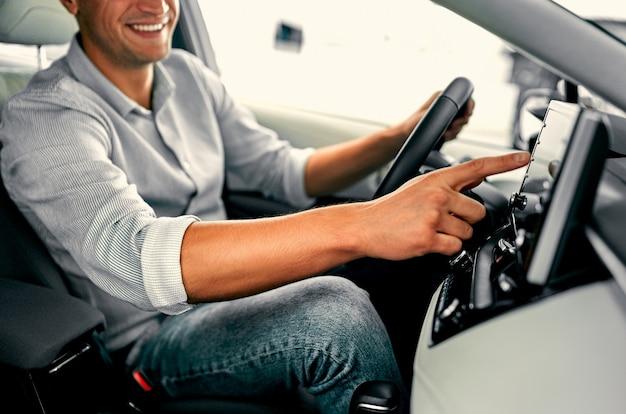 Обрезанное изображение руки человека с помощью навигационной системы во время вождения автомобиля.