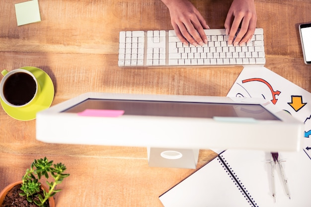Cropped image of hands typing on computer keyboard at desk in creative office