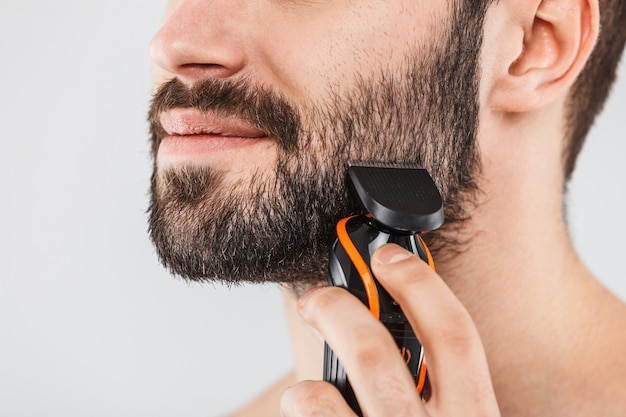 Cropped image of a handsome bearded man shaving with an electric razor isolated over white