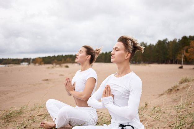 Cropped image of handsome guy practicing meditation with blonde woman, sitting on sand in lotus pose, closing eyes, having peaceful facial expressions.