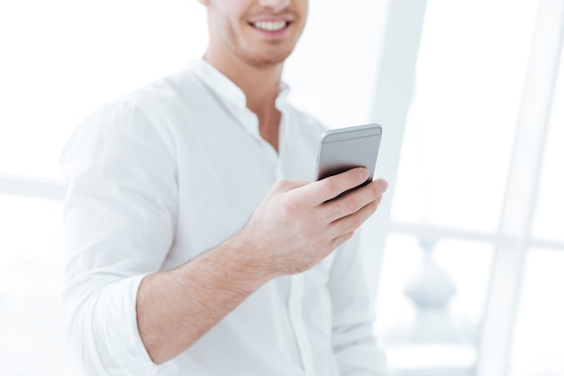 Cropped image of handsome man dressed in white shirt chatting by phone near big white window.