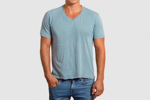 Cropped image of handsome man wears blank t shirt, keeps hand in pocket, dressed in jeans, isolated on white. unrecognizable male advertises new outfit. people and fashion concept
