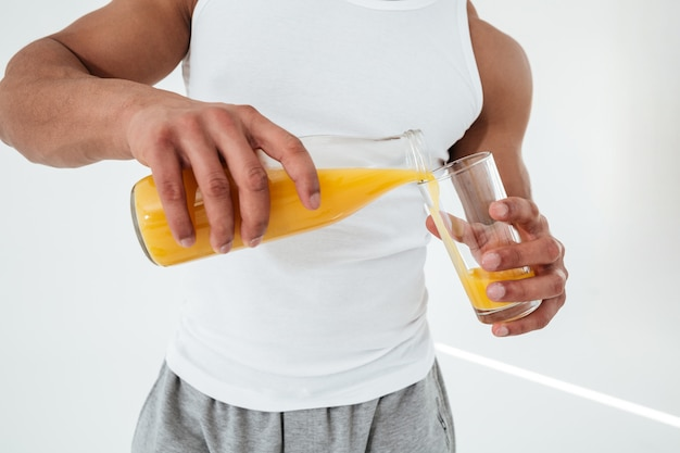 Cropped image of handsome young sportsman holding glass of juice.