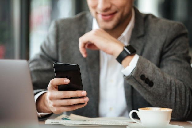 Cropped image of happy businessman sitting by the table in cafe and using smartphone
