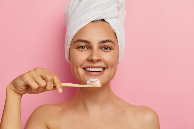 Cropped image of happy european woman brushes teeth, holds toothbrush with toothpaste, wears wrapped towel on head, has healthy fresh skin, stands naked