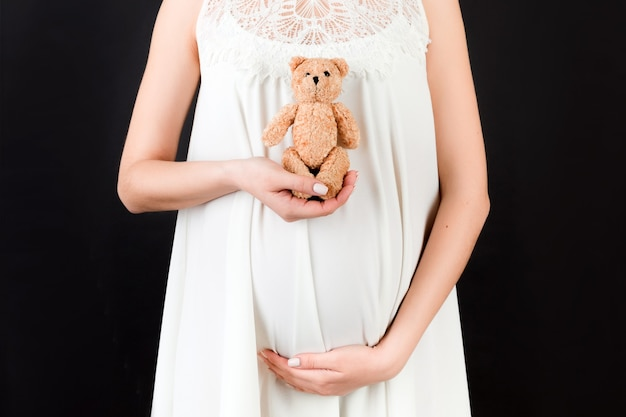 Cropped image of happy pregnant woman in white dress holding teddy bear against her belly at black background. child expecting. copy space.