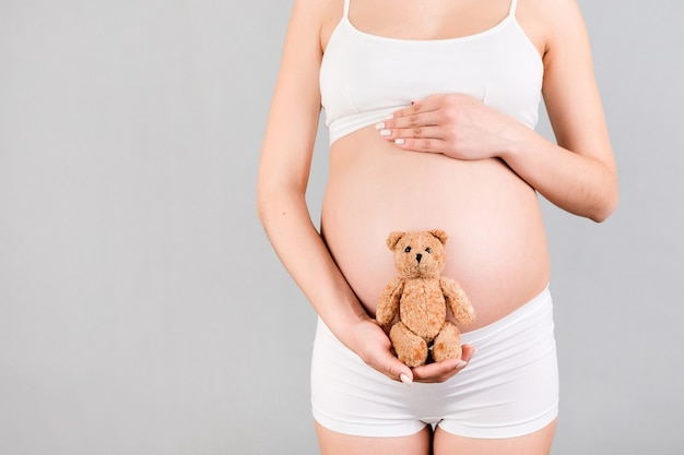 Cropped image of happy pregnant woman in white underwear holding teddy bear against her belly at gray background. child expecting. copy space.