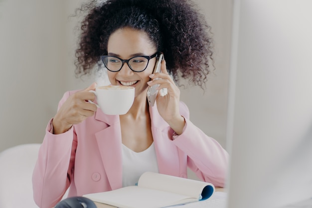 Cropped image of happy young woman makes phone call and drinks aromatic latte