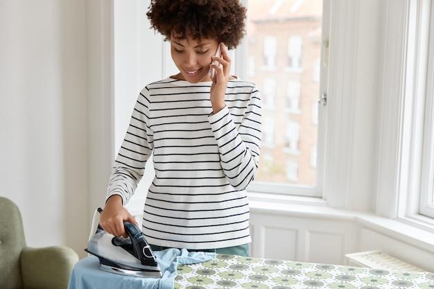 L'immagine ritagliata della casalinga ha una conversazione telefonica mentre stira i vestiti durante il fine settimana a casa