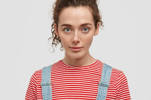 Cropped image of lovely young green eyed curly female looks seriously, dressed in casual outfit, listens something attentively, isolated on white wall. close up of freckled woman