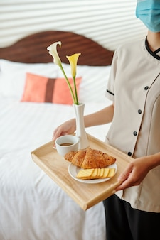 Cropped image of maid bringing fresh coffee, croissant and cookies in hotel room of guest