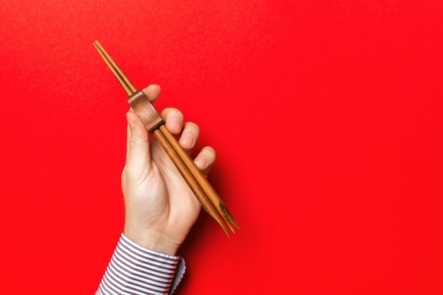 Cropped image of male hand holding chopsticks on red background. asian food concept with copy space.