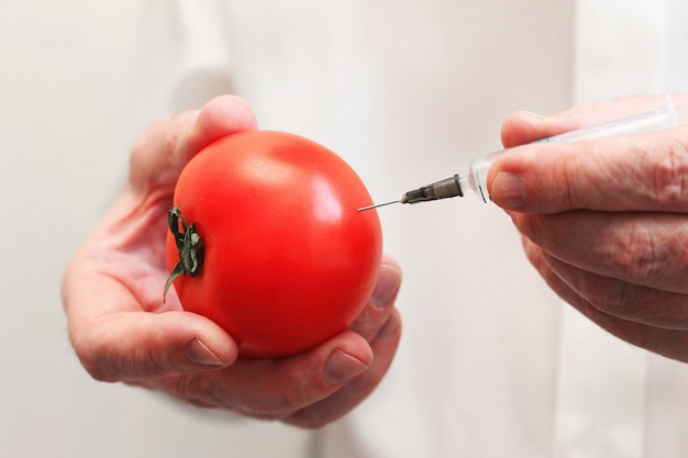 Cropped image of a male scientist dressed in uniform making a syringe shot in a tomato