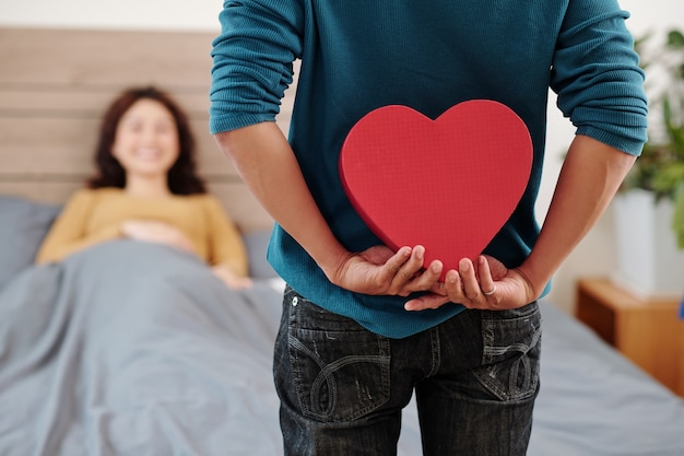 Cropped image of man hiding romantic present behind his back when standing at bed of girlfriend who just woke up