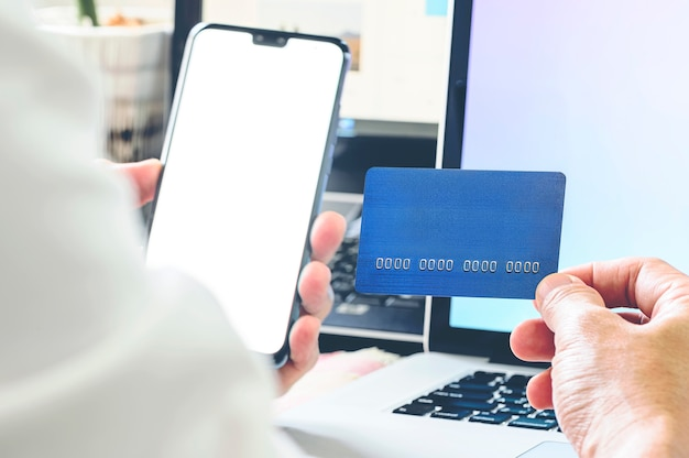 Cropped image of man holding credit card and using smartphone while,sitting at office desk.