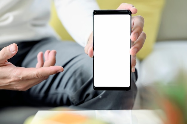 Cropped image of man holding and showing blank screen of smartphone while sitting at home