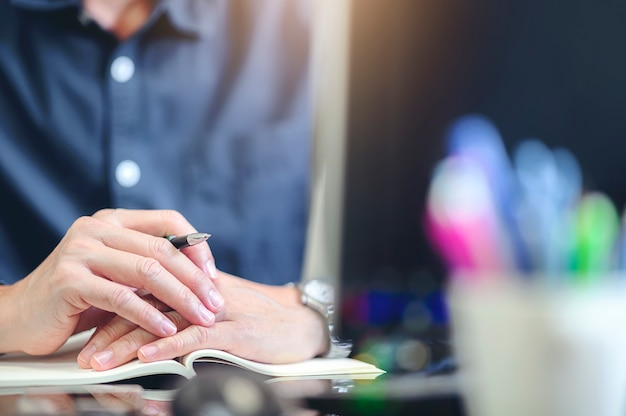 Cropped image of man sitting at office desk holding pen and puting hands together.