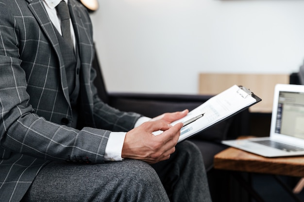 Cropped image of a man in suit analyzing documents