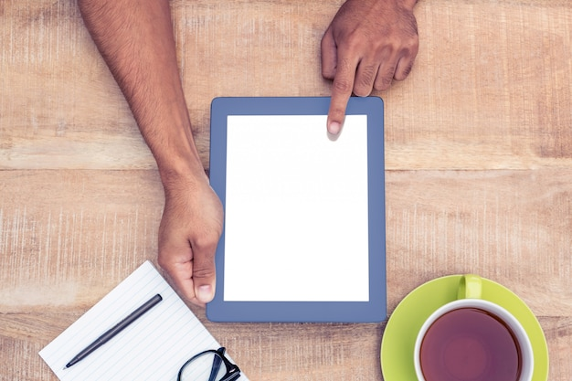 Cropped image of man using on digital tablet by coffee and document on table