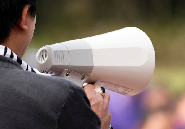 Cropped image of man using  a megaphone at the park