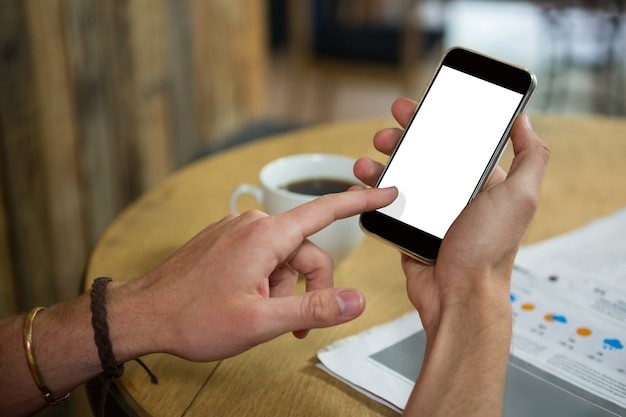 Cropped image of man using mobile phone at table in cafeteria