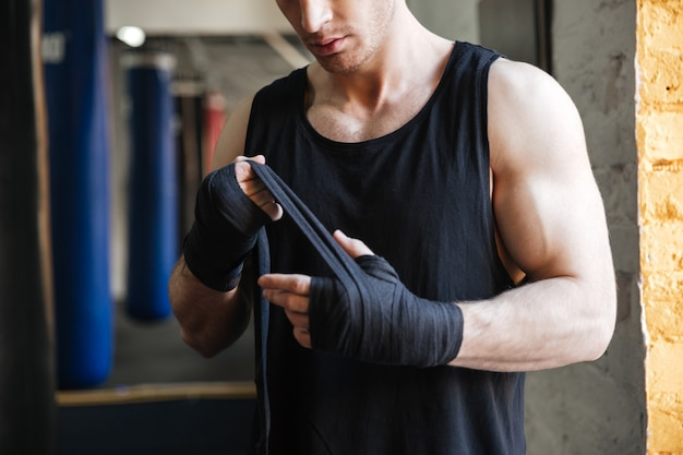 Cropped image of man wearing gloves for boxing