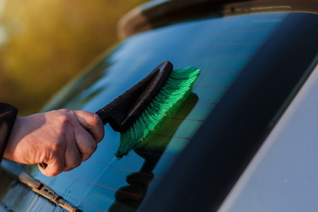 Cropped image of manual washer cleaning car at service station