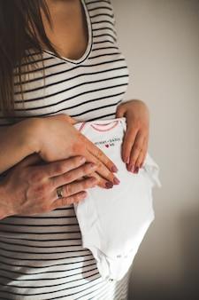 美しい妊婦とハンサムな夫がおなかを抱いて小さな子供服を持っている画像をトリミングしました。幸福。母親と赤ちゃんのテーマ。
