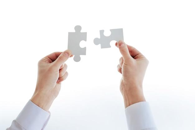 パズルのピースを見ているビジネスマンのトリミングされた画像。コピースペース付きの写真。