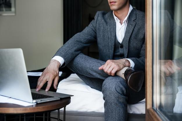 ベッドの上に座っているビジネスマンのトリミングされた画像