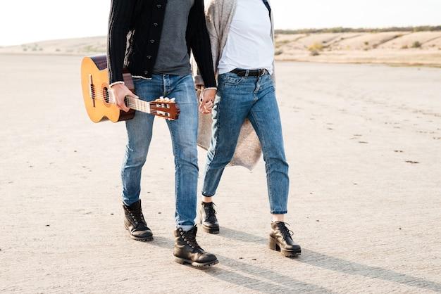 기타와 함께 해변에서 산책하는 캐주얼 커플의 자른 이미지