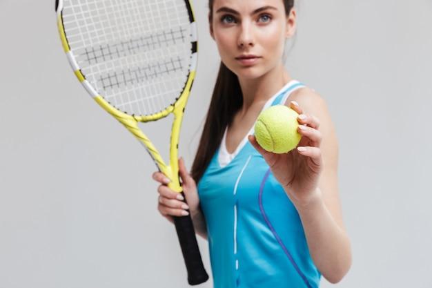 灰色の壁に隔離されたラケットとボールを保持している自信のある女性テニスプレーヤーのトリミングされた画像