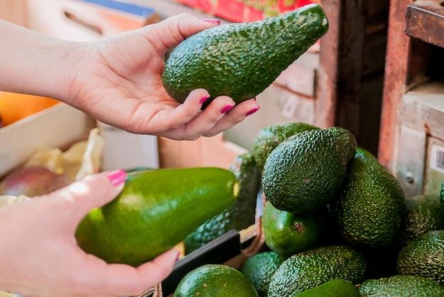 スーパーマーケットでアボカドを選んだ顧客のイメージを切り取ったもの。市場でアボカドを持つ女性の手を閉じます。販売、ショッピング、食品、消費者主義、人々のコンセプト