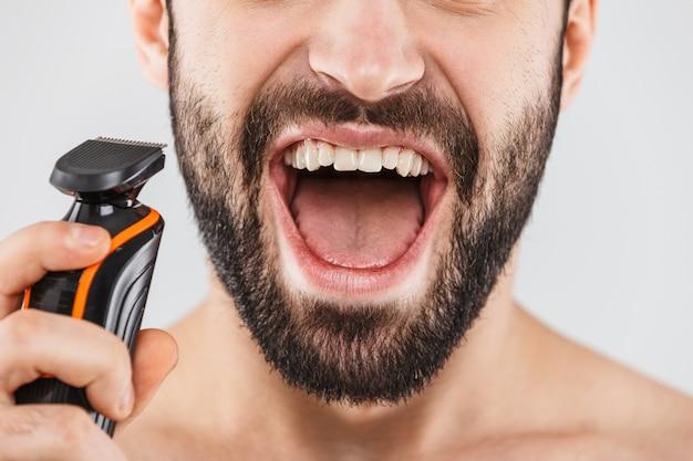 Обрезанное изображение красивого бородатого мужчины, бреющегося электрической бритвой, изолированного на белом