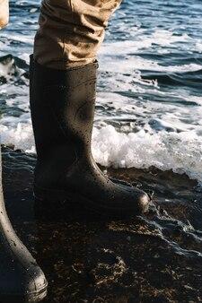 海岸でハンサムな男の漁師のトリミングされた画像。