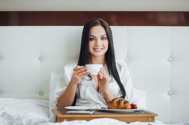 バラの花束と一緒にベッドに座って、朝のトレイでコーヒーとクロワッサンを食べる幸せなブルネットの少女のトリミングされた画像