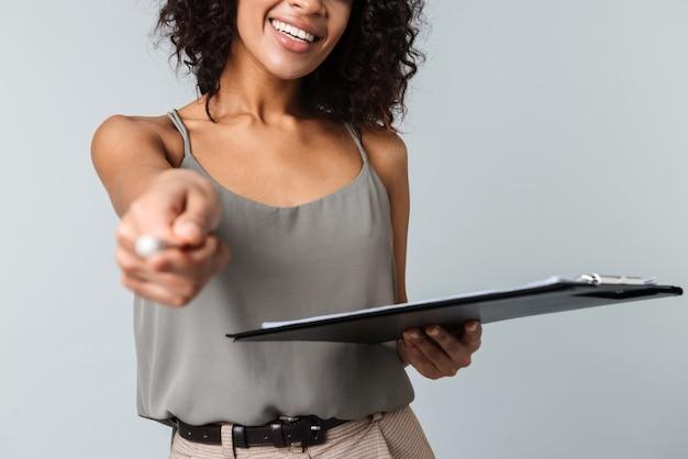 幸せな若いアフリカの女性のトリミングされた画像は、孤立して立って、メモ帳を持って、ペンで指しているカジュアルな服を着ています