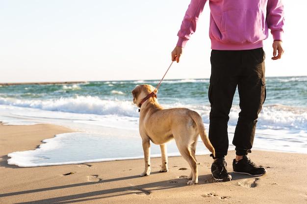 그의 강아지와 함께 해변에서 산책하는 남자의 자른 이미지