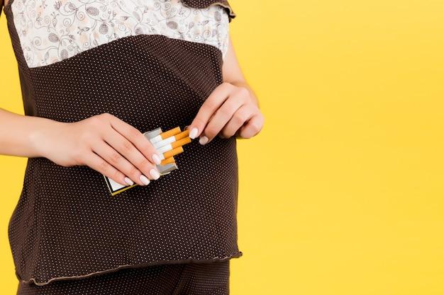 노란색 배경에서 담배 한 갑의 자른 이미지. 갈색 잠옷을 입은 임산부의 나쁜 습관. 부주의 한 어머니.