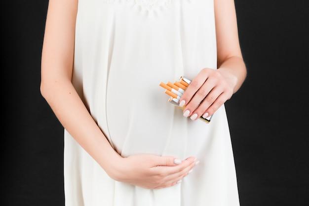 검은 배경에서 임신한 여성의 손에 있는 담배 한 갑의 자른 이미지. 낙태 위험. 흡연 중독. 위험한 습관.