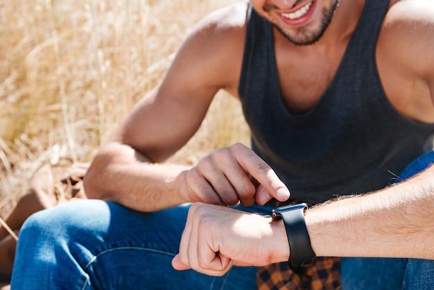 야외에서 앉아있는 동안 스마트 시계를 사용하여 웃는 남자의 자른 이미지