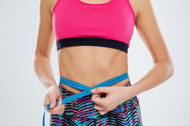 Обрезанное изображение спортивной женщины, измеряющей талию с лентой