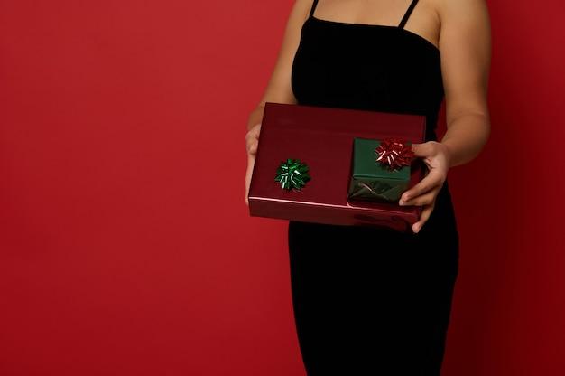 세련된 이브닝 블랙 벨벳 드레스를 입은 여성의 자른 이미지가 빨간색 배경에 빨간색과 녹색 선물 종이를 감싸는 반짝이는 크리스마스 선물과 함께 포즈를 취합니다. 광고 복사 공간이 있는 새해 개념