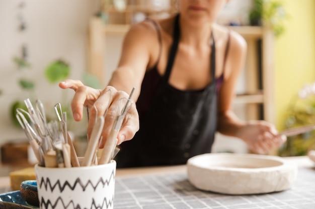 Обрезанное изображение женщины, делающей керамическую и гончарную посуду в мастерской